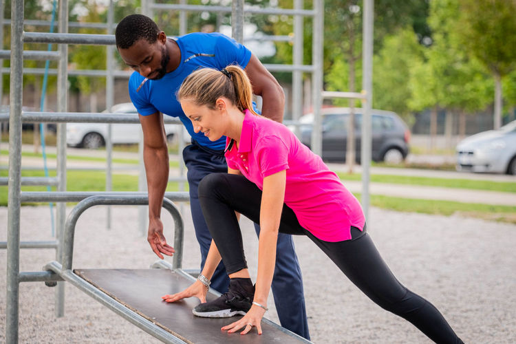 Fitness instructor guiding woman in exercise at park