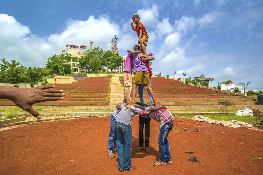 Little Mahesh, 10 years old, at the top of the human pyramid, practising for the Dahi Handi festival that took place recently. The Indian government banned kids below 12 years participating, as many people get injured. The main aim is to build a pyramid high enough to break open a high dangling clay pot full of butter, thereby winning a cash prize. Traveling Streetphotography Collected Community RePicture Team Having Fun Under Pressure Collected Comunity