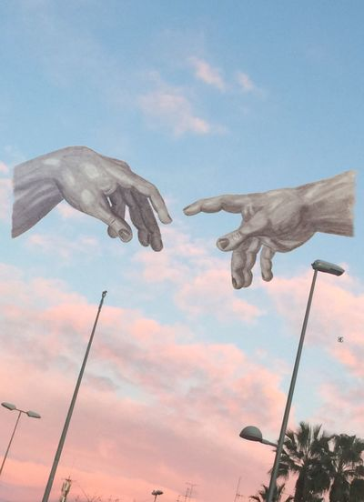 Low angle view of hand against sky at sunset
