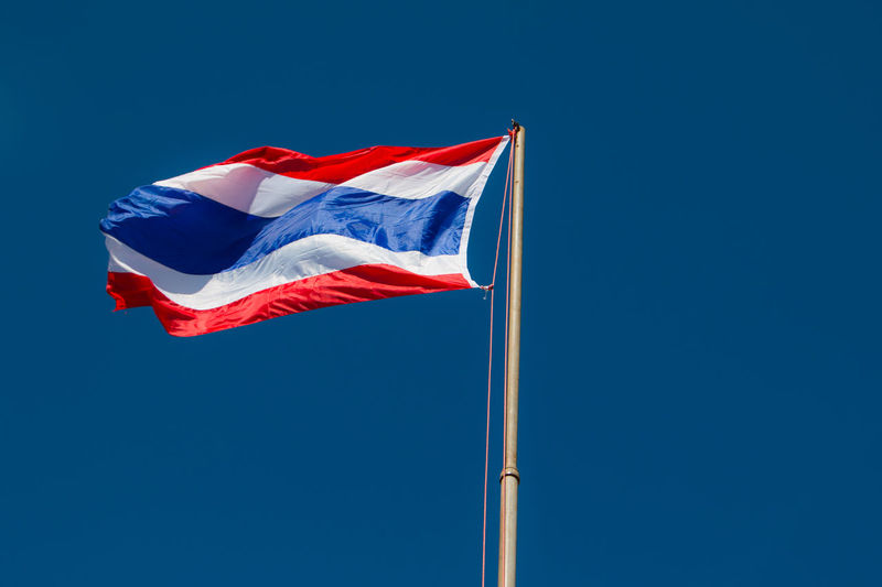 Low angle view of thai flag waving against clear blue sky