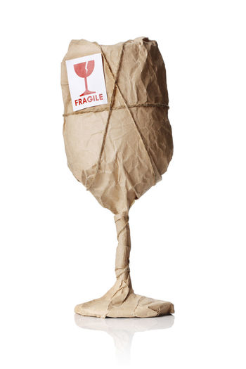 "A Wine glass packaged in brown wrapping paper with ""Fragile"" warning sticker."