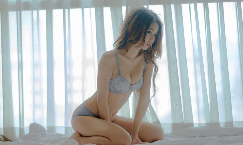 Beautiful young woman in bikini kneeling on bed at home