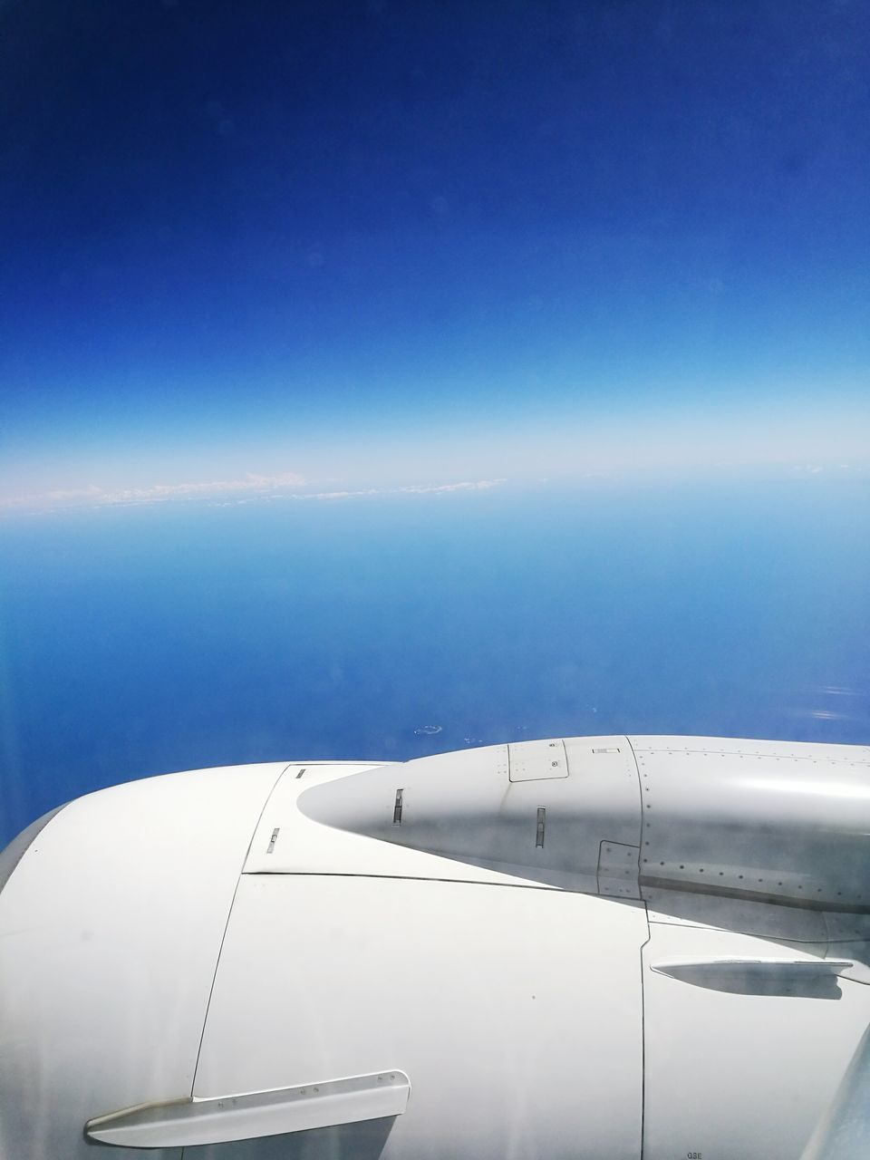 airplane, transportation, journey, air vehicle, mode of transport, blue, jet engine, airplane wing, no people, travel, aircraft wing, aerial view, day, flying, outdoors, mid-air, sky, sea, nature, close-up