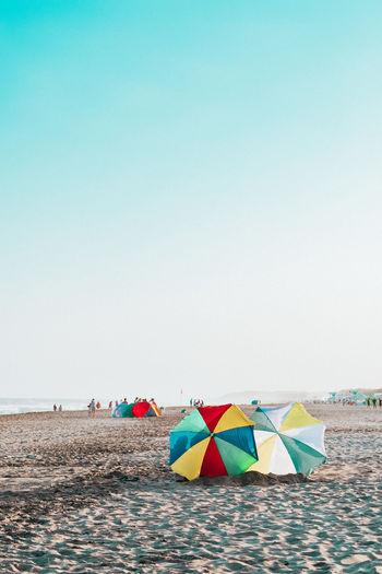 Colorful umbrellas on beach against clear sky