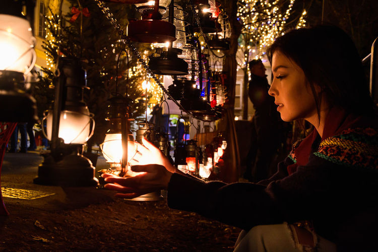Young Woman Looking Illuminated Lanterns In Store At Night