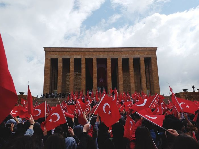 Crowd of people holding turkish flag against building