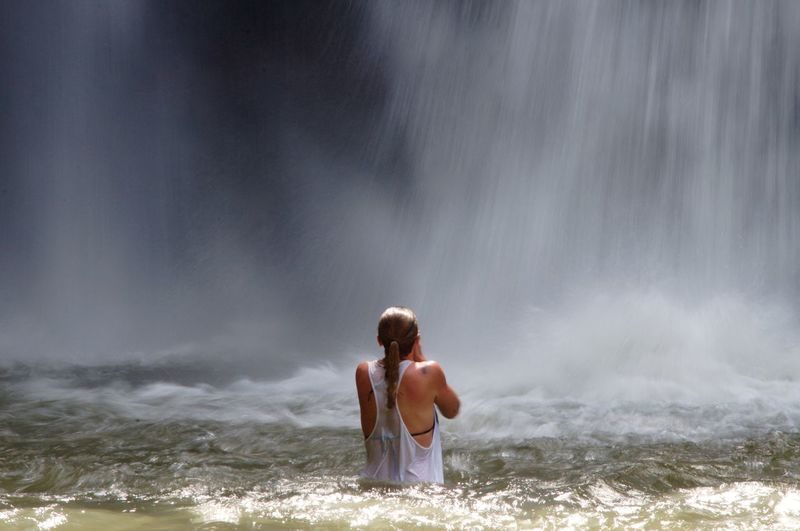 Rear View Of Woman Standing In River By Waterfall
