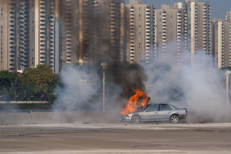 Burning car on road against buildings in city