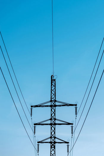 High voltage electricity transmission metallic tower pole dark silhouette in blue evening sky