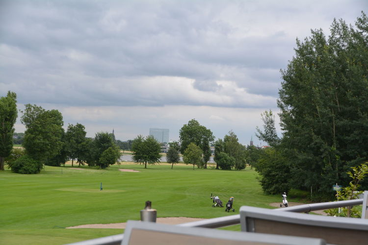 Scenic view of green golf course against cloudy sky