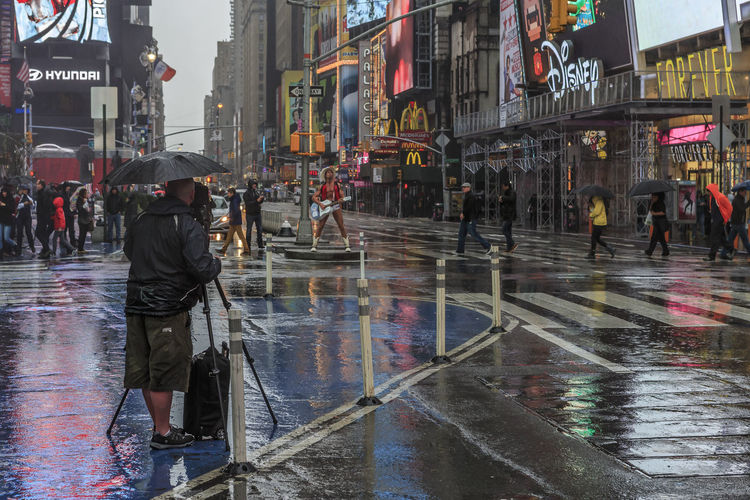 Sometimes you wish you had stayed home from work :-) Water Wet Rain City Architecture Real People Building Exterior Street Built Structure Rainy Season Umbrella Monsoon Incidental People Protection City Life Walking Men People City Street Performer  Photograper Filming Times Square NYC Cowboy