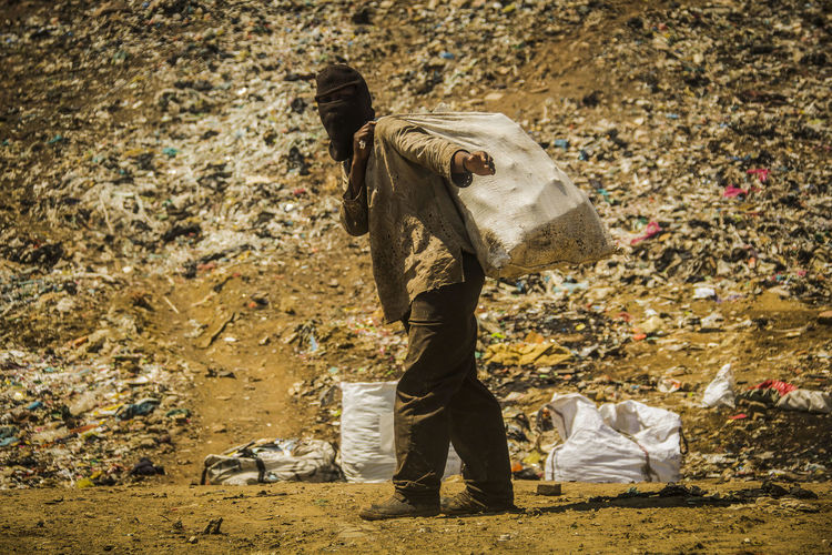 Man standing by garbage on field