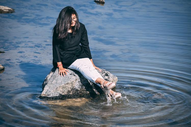 Young woman splashing water while sitting on rock in sea