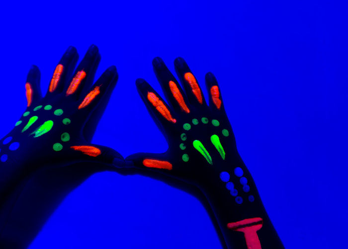 Close-Up Of Neon Painted Hand Against Blue Wall. Hand Abstract Neon Background Paint Art Design Colorful Bright Color Fashion Creative Fantasy Light Black Party Glow Purple Night Texture Style Beautiful Beauty Makeup Glowing Ultraviolet Dark Fluorescent UV  Splash Club Disco Woman Blue Yellow Shape Violet Face Make Graphic