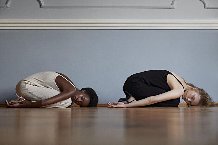 Side view of young women exercising on hardwood floor