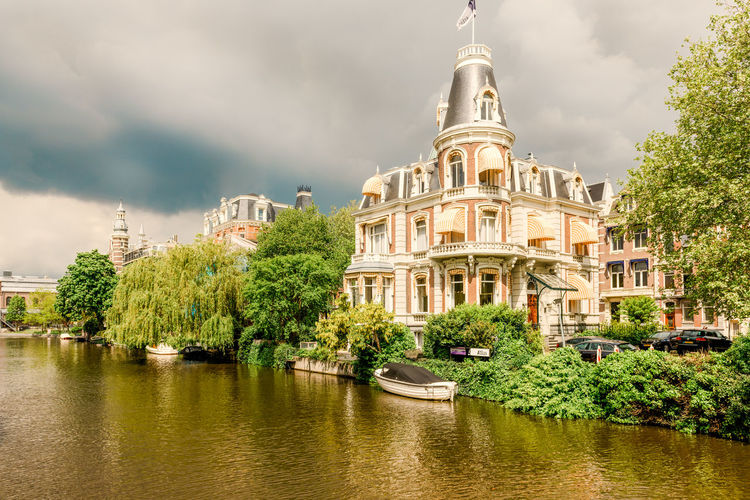 An Old Building in Amsterdam Tree Plant Water Built Structure Cloud - Sky Building Exterior Sky Architecture Nature Waterfront River Building Day Outdoors Transportation No People Mode Of Transportation Travel Destinations Nautical Vessel Amsterdam