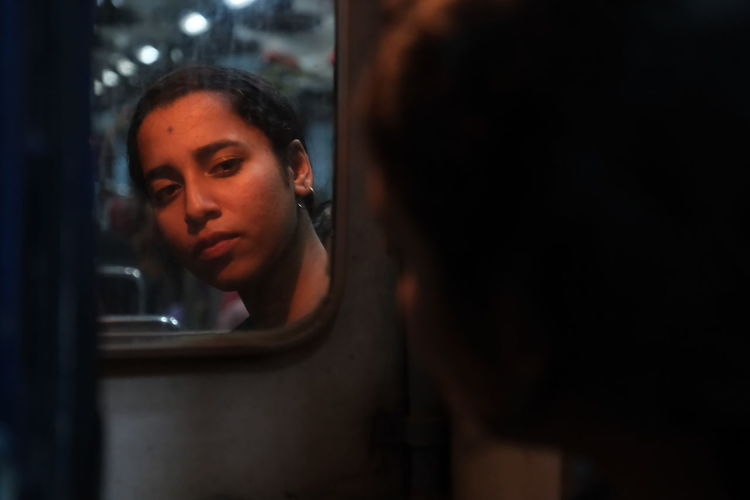 Young woman reflecting on mirror in train