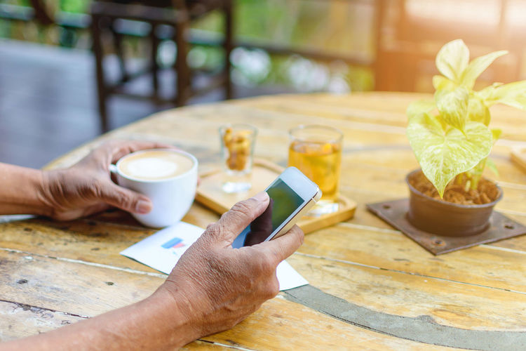 Cropped hands of man holding smart phone and coffee cup at cafe