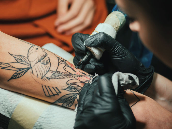 Cropped image of female artist making tattoo on male customer hand