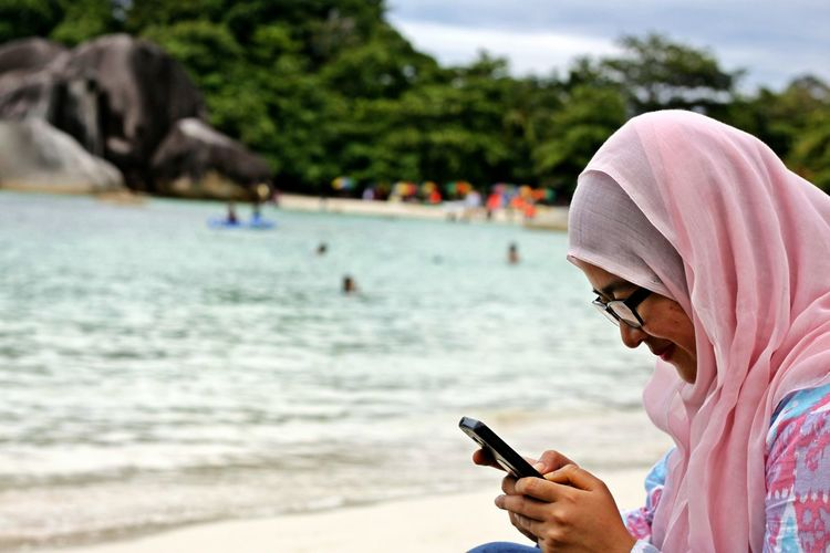 Adult Adults Only Beach Close-up Communication Day Focus On Foreground Holding Lifestyles Mobile Phone One Man Only One Person Outdoors People Portable Information Device Real People Sea Sky Smart Phone Technology Tree Warm Clothing Water Wireless Technology
