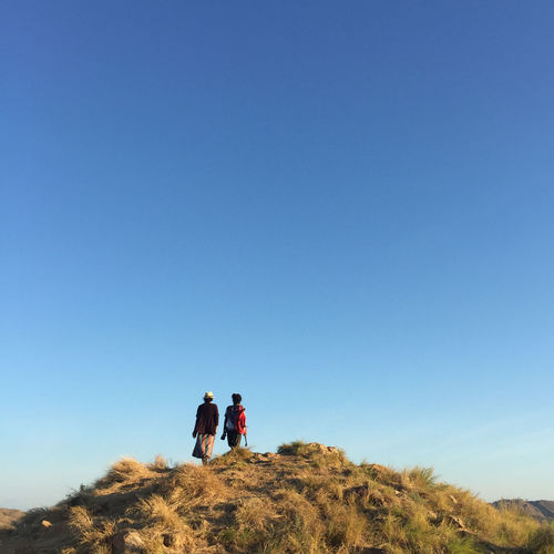 Rear view of people walking on mountain against clear blue sky