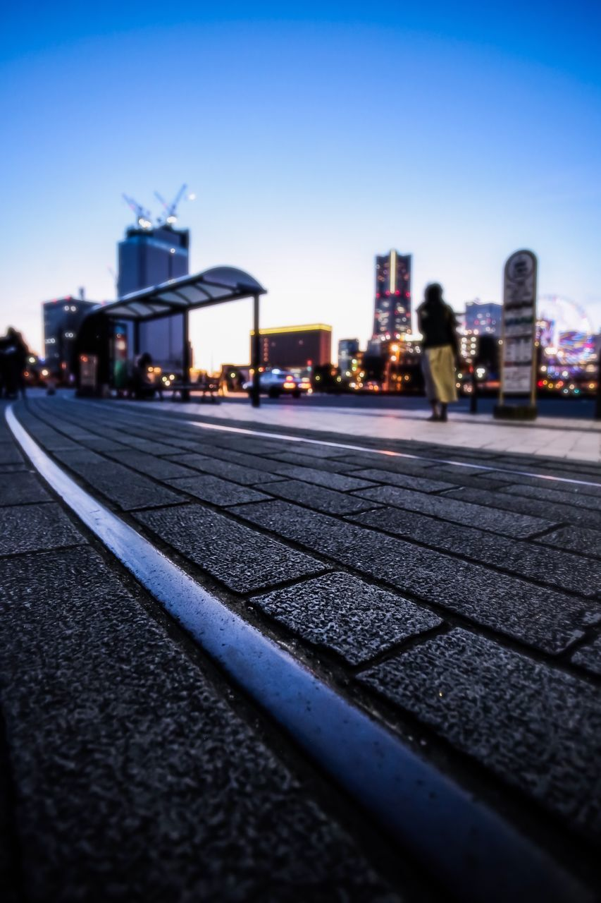 sky, building exterior, city, architecture, built structure, street, transportation, no people, nature, clear sky, outdoors, road, surface level, illuminated, dusk, building, selective focus, day, city life, blue, office building exterior, skyscraper