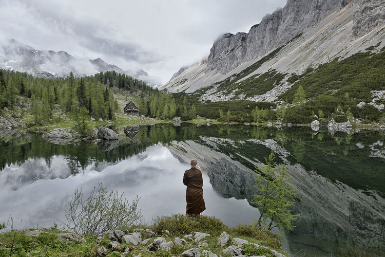 Rear view of monk standing by lake with mountains reflection