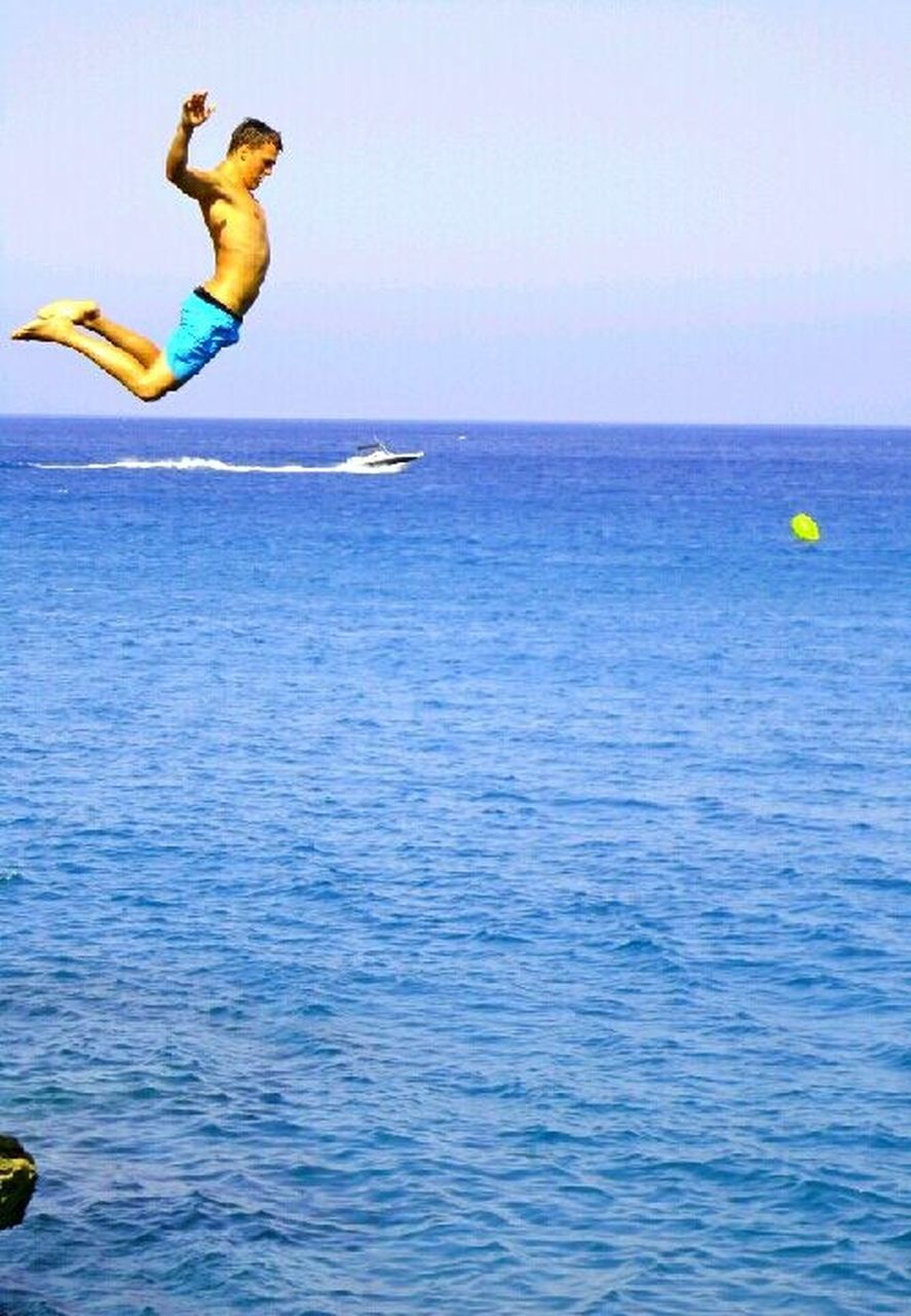 mid-air, sea, jumping, full length, flying, horizon over water, blue, activity, vitality, water, one person, motion, sport, leisure activity, outdoors, clear sky, fun, excitement, sky, vacations, people, adventure, one man only, day, nature, swimming, stunt, only men, adult, adults only, young adult