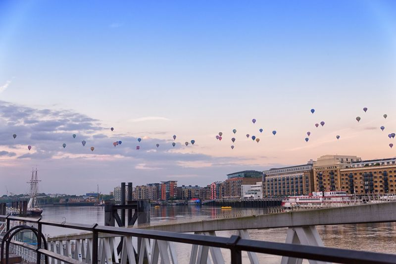 Hot air balloons over river and buildings against sky at dusk in city