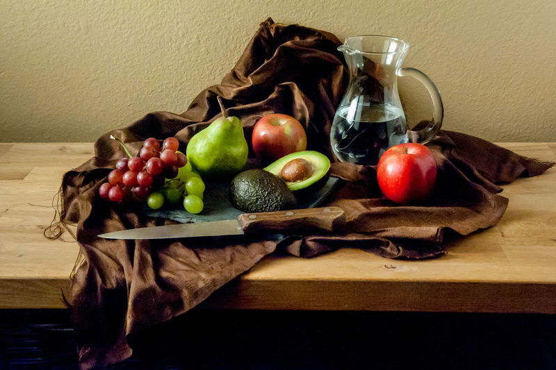 High angle view of fresh fruits with water and knife on table