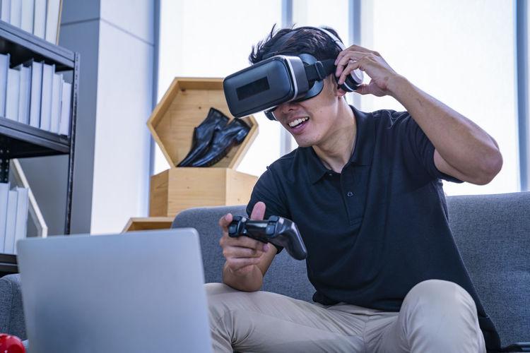 Man playing video game wearing virtual simulator while sitting at home