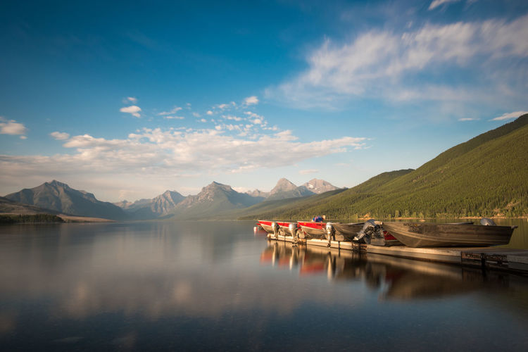 Boats on an empty Lake McDonald with mountains in the back Fishing Boats Lake Life Lake Mcdonald Montana Beauty In Nature Boat Cloud - Sky Day Dock Fishing Boat Glacier National Park Lake Motor Boats Mountain Mountain Range Nature Outdoors Reflection Scenics Sky Tranquil Scene Tranquility Water Waterfront