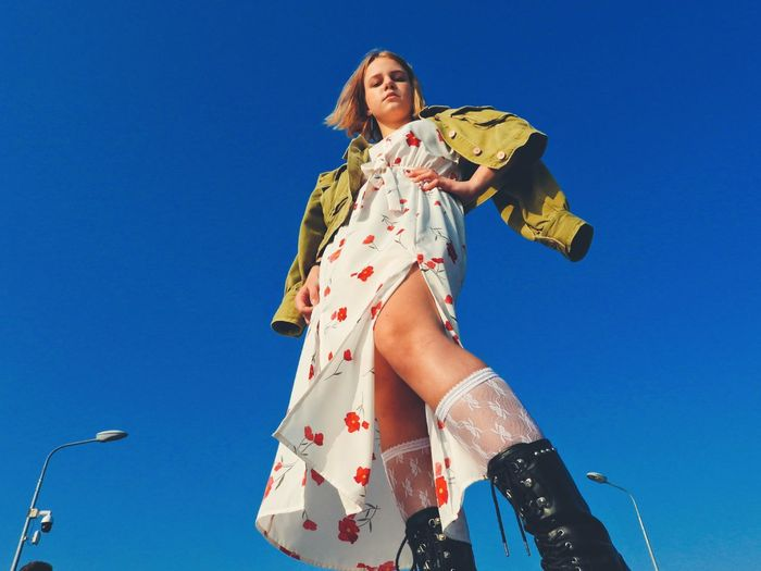 Low angle view of girl against blue sky