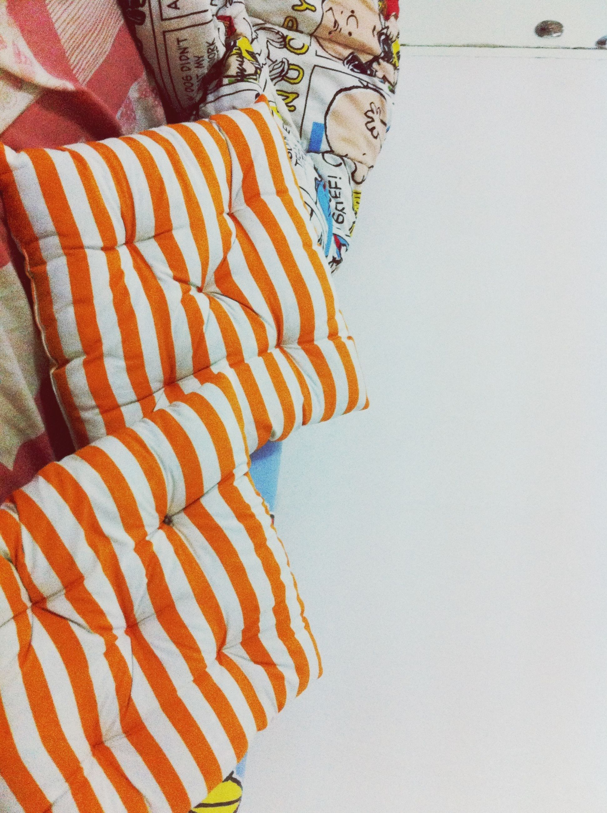 striped, pattern, indoors, high angle view, design, multi colored, creativity, art and craft, art, fabric, white color, no people, textile, close-up, wall - building feature, blue, day, shadow, sunlight, orange color