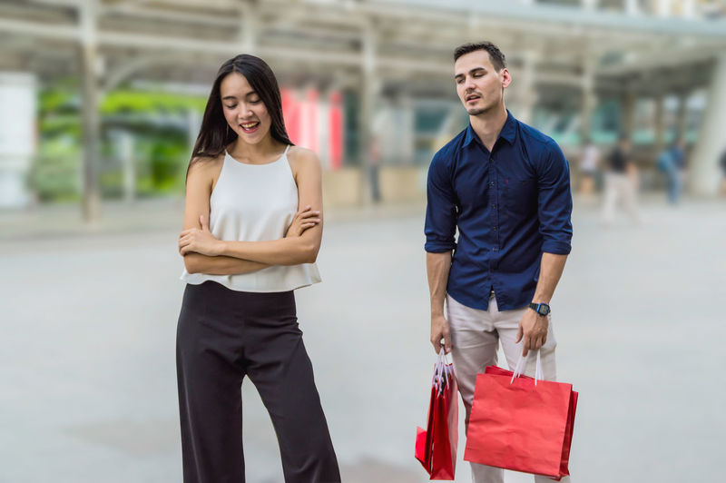 happy young couple with shopping bags walking in mall Asian  Attractive Background Bags Beautiful Bored Boyfriend Buyers Caucasian Center Cheerful City Clothes Commercial Consumer Consumerism Consumption  Couple Customer  Elegant Family Fashion Female Friends Gifts Girlfriend Glad Happy Hispanic Holding Husband Joyful Lifestyle Male Mall Man person Presents Pretty Purchase Purchasing Retail  Sale Sell Shopping Smile Tired Wife WOW Young