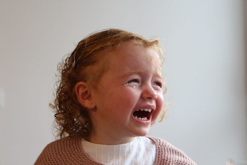 Close-Up Of Girl Crying Against White Background