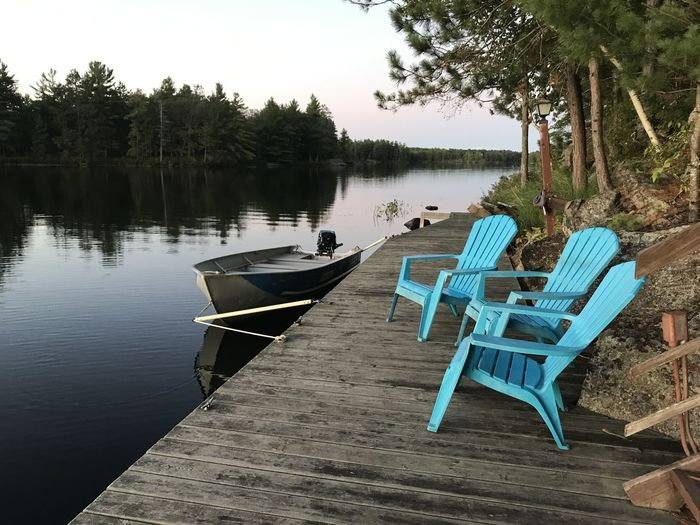 Chairs on lake by trees against sky