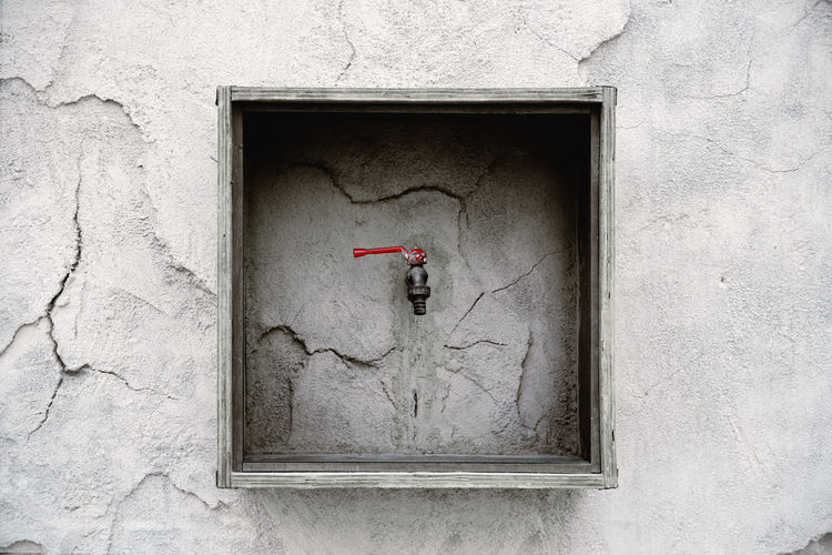 Faucet On Concrete Cracked Wall