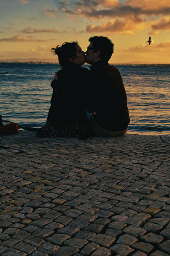 Couple sitting on shore against sky during sunset
