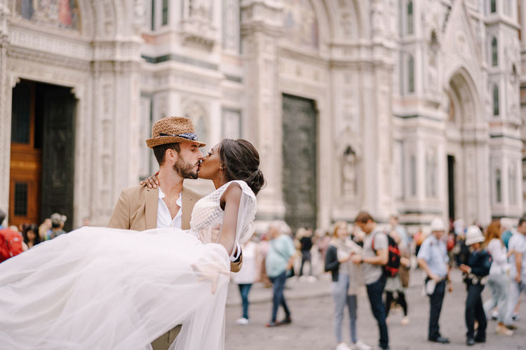 Couple kissing in front of building on street