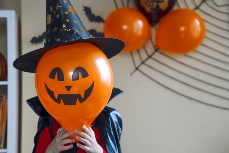 Low angle view of person holding pumpkin at home during halloween
