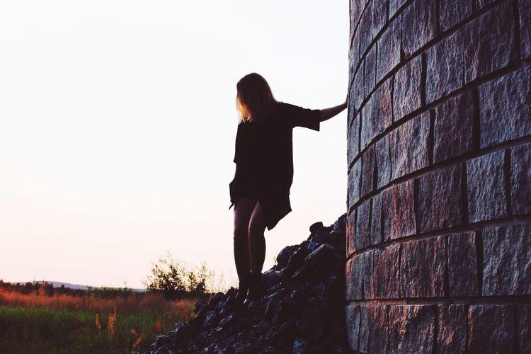 Woman On Stone Heap Against Clear Sky