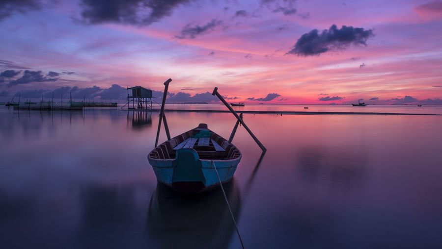 Fishing boat moored in lake against sky during sunset