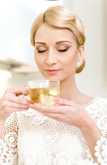Portrait of beautiful girl drinking tea Aroma Aromatic Attractive Beautiful Woman Blond Hair Caucasian Cup Drink Drinking Drinking Tea Enjoyment Female Green Tea Healthy Lifestyle Heat Herb Tea Holding Indoors  Kitchen Lady One Person Relaxation Serene Tea Woman