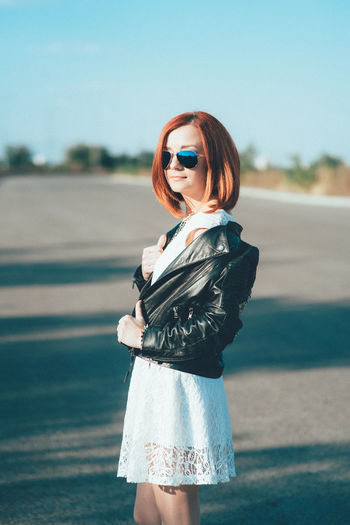 Woman wearing sunglasses standing on road against sky