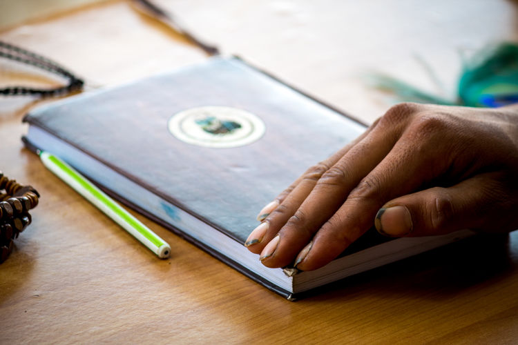 Cropped hand on diary over table