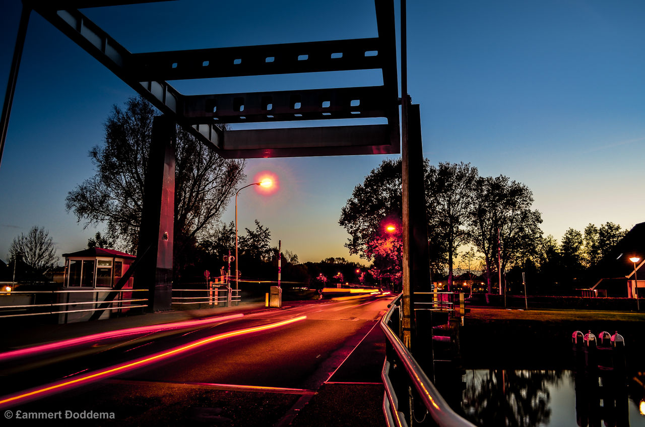 tree, transportation, the way forward, red, bridge - man made structure, speed, sky, illuminated, road, outdoors, no people, clear sky, architecture, day, city, nature
