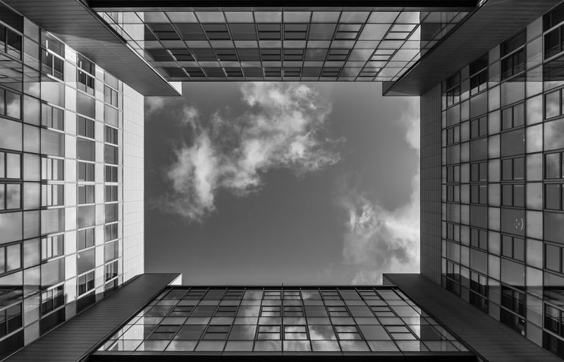 Directly Below Shot Of Glass Building With Skylight Against Sky