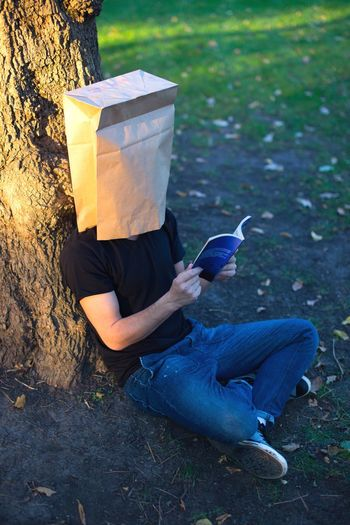High Angle View Of Man Wearing Paper Bag While Reading Book Outdoors