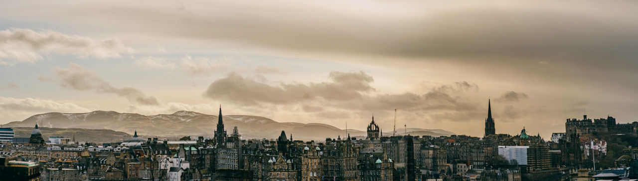 Panoramic view of buildings against cloudy sky and hills